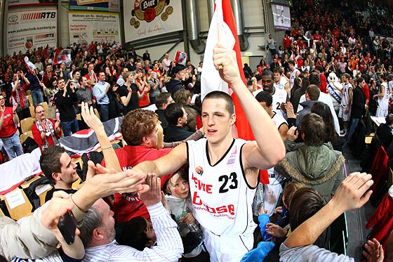 Casey Jacobsen (Bamberg) feiert nach dem Sieg zwischen den Fans mit einer Franken-Fahne in der Hand