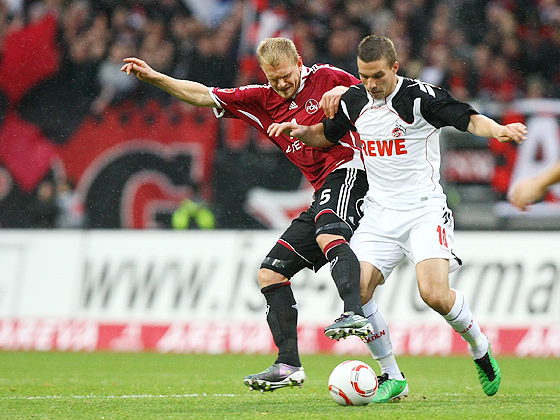 Andreas Wolf (Nürnberg) hat Lukas Podolski (Köln) im Zweikampf im Griff.